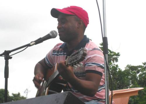 """El cantautor Juan Dionisio participa en el concierto, compartiendo canciones de denuncia y poder popular. Su canción """"El bacá"""" trata de """"un animal misterioso"""" con macana que amenaza al pueblo."""